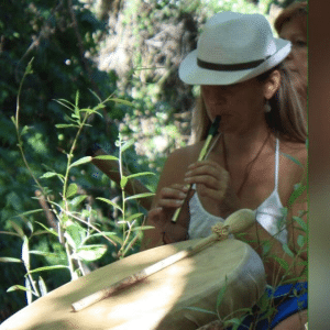 laetitia Djian qui joue de la flûte devant un tambour chamnique